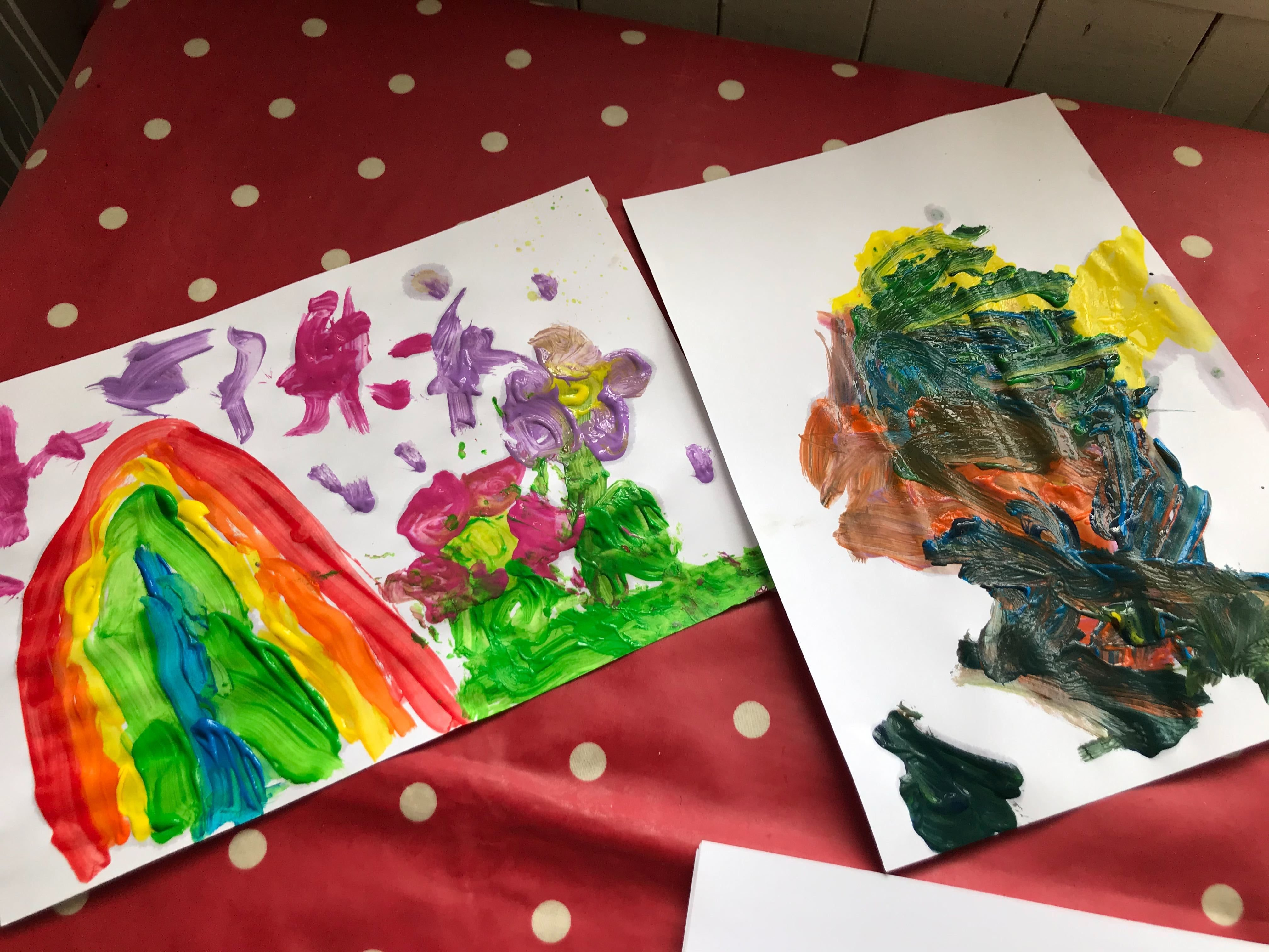 Two children's paintings of colourful rainbows on a table