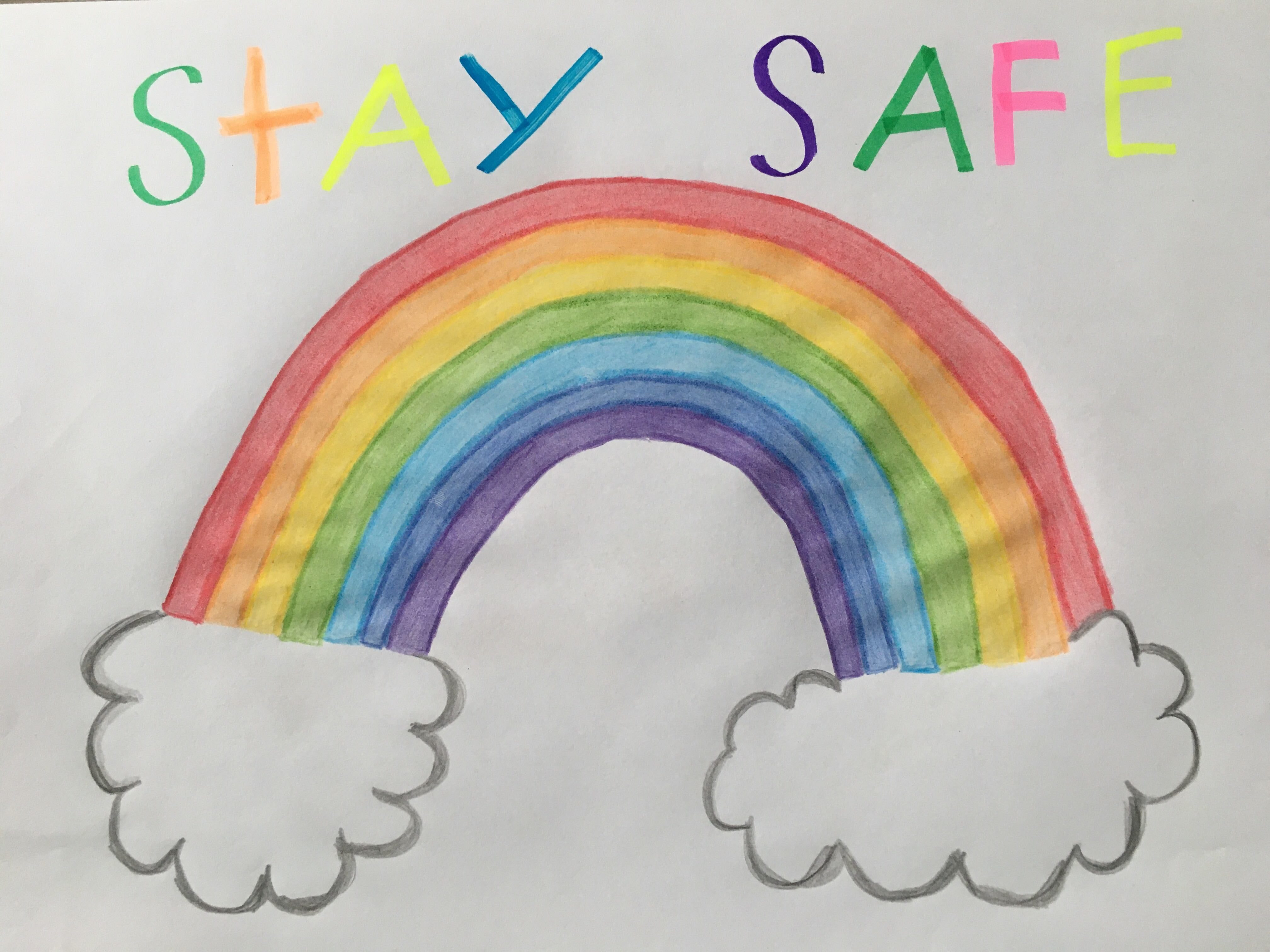 Children's drawing of a rainbow with the words 'stay safe' written above it