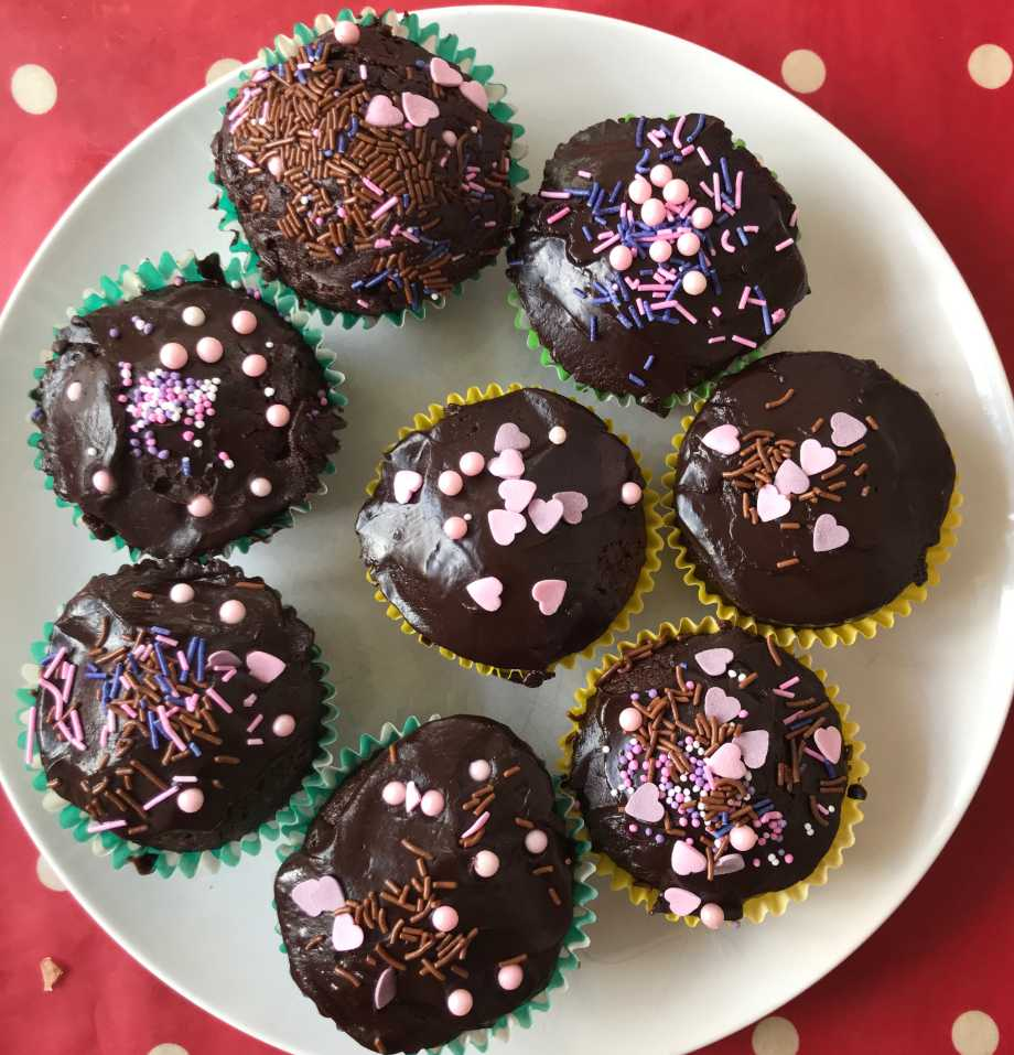Plate of 8 chocolate cupcakes with pink heart sprinkles