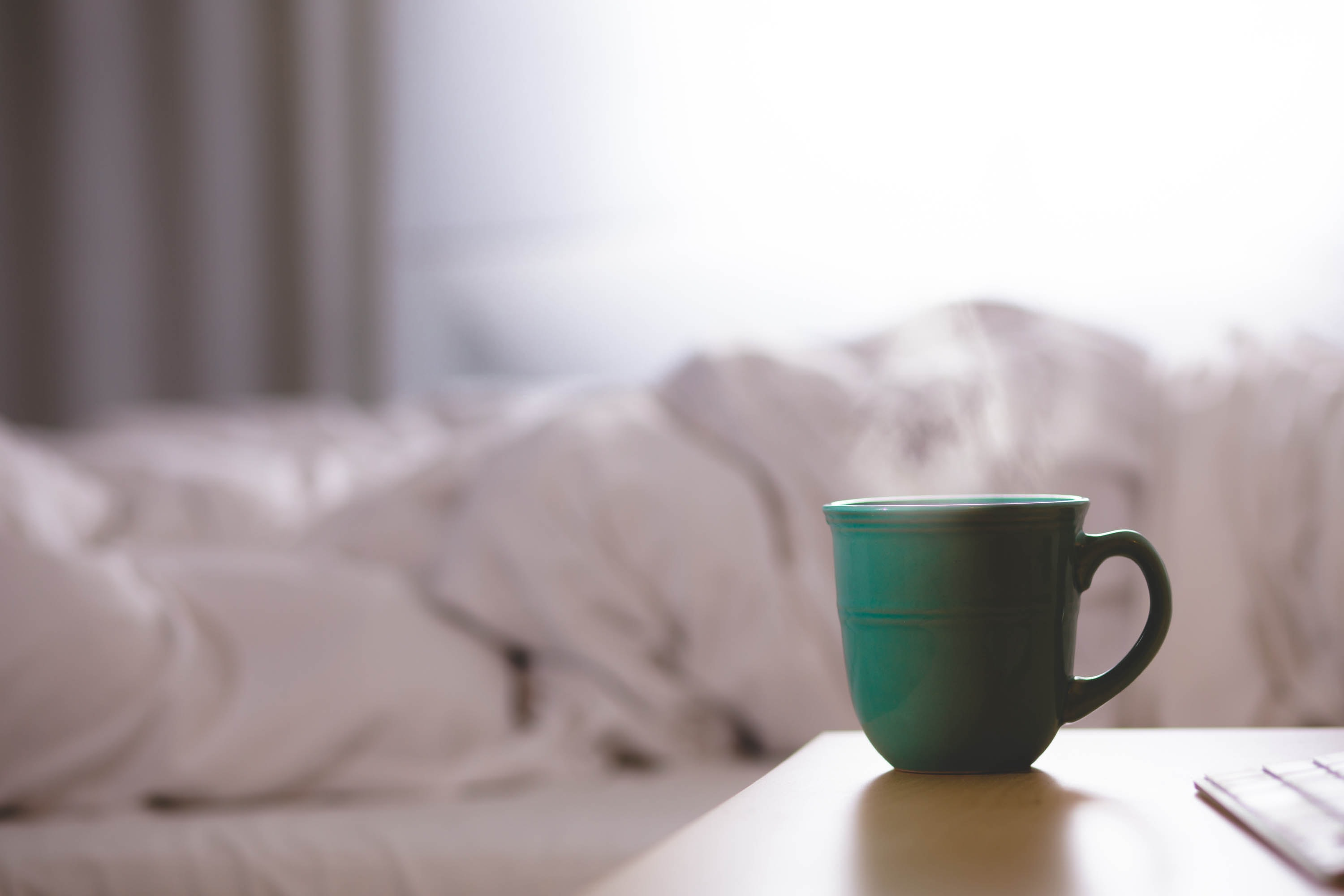 Green steaming teacup on bedside table with big white comforter on bed in background