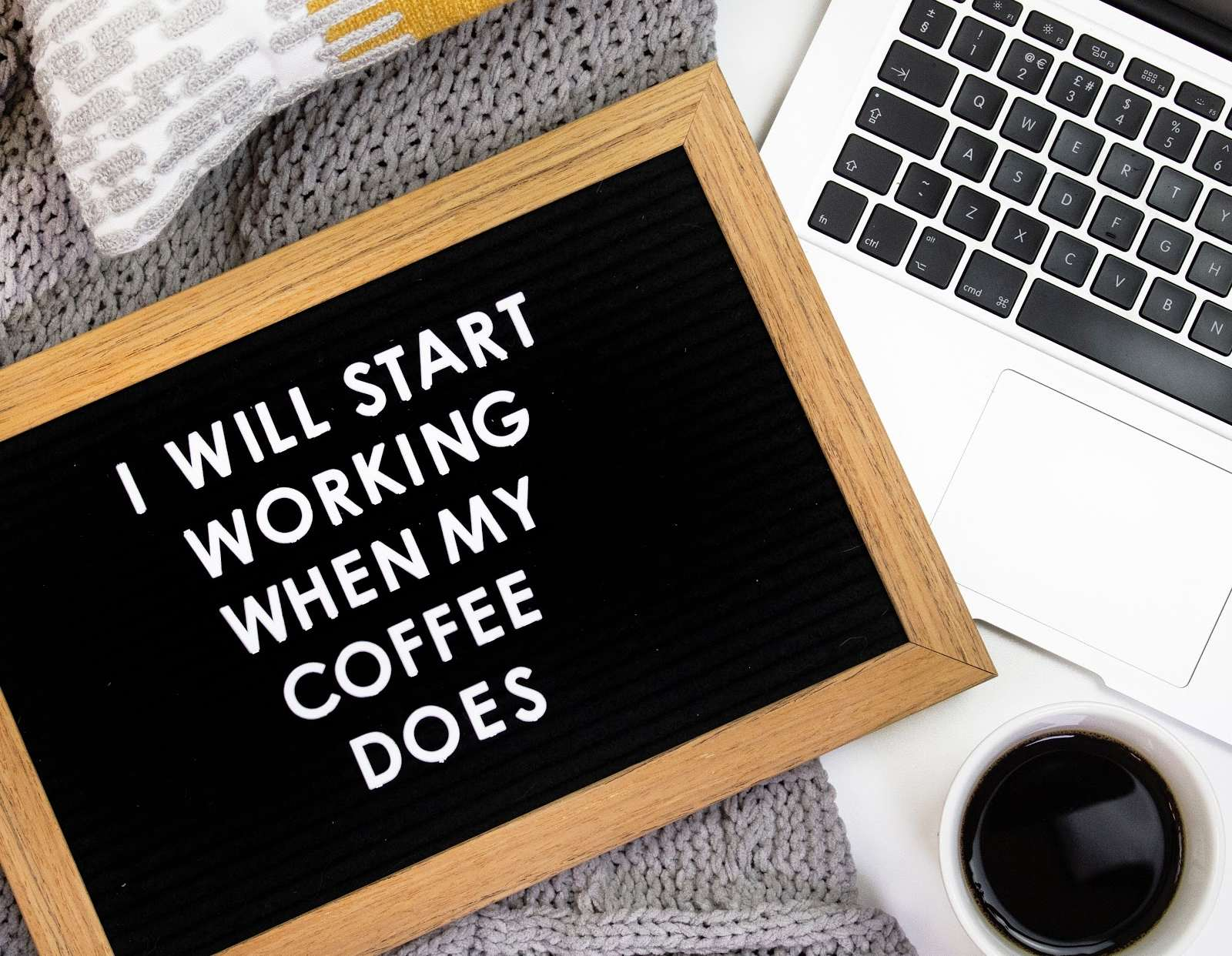 Black sign with white writing that says 'I will start working when my coffee does' beside Macbook and cup of black coffee on grey wooly blanket