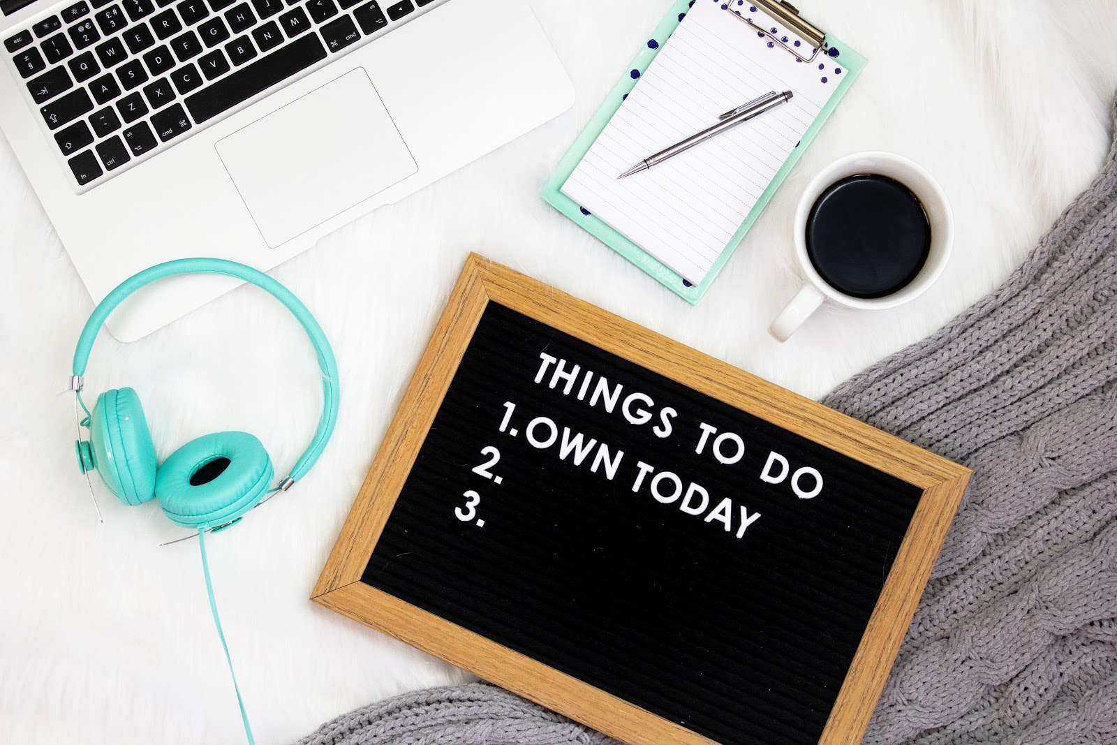 Black sign that says 'Things to do 1. Own Today' beside turquoise headphones and notebook, beside a cup of black coffee and the keyboard of a Macbook