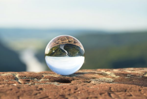 Glass marble showing the reflection of a valley with a river flowing through