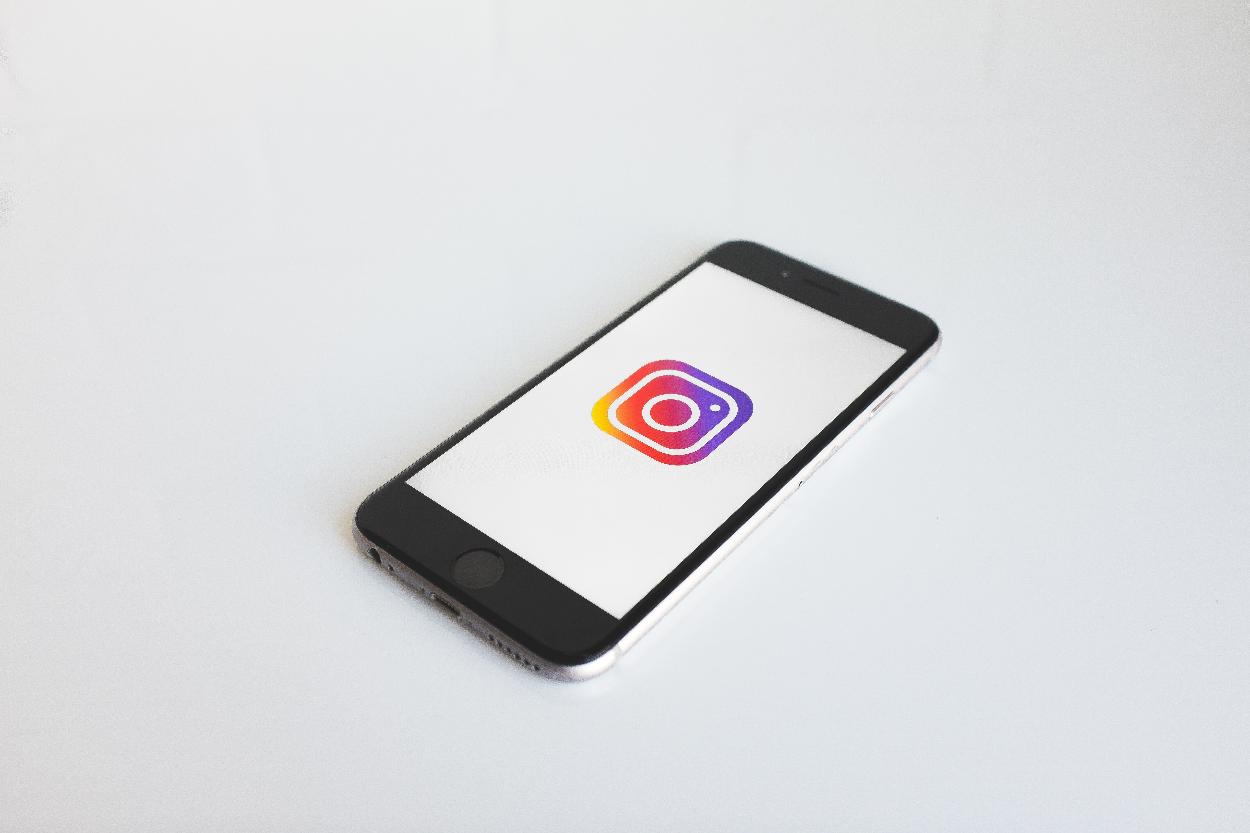 iPhone on white surface showing screen of large Instagram logo on white background