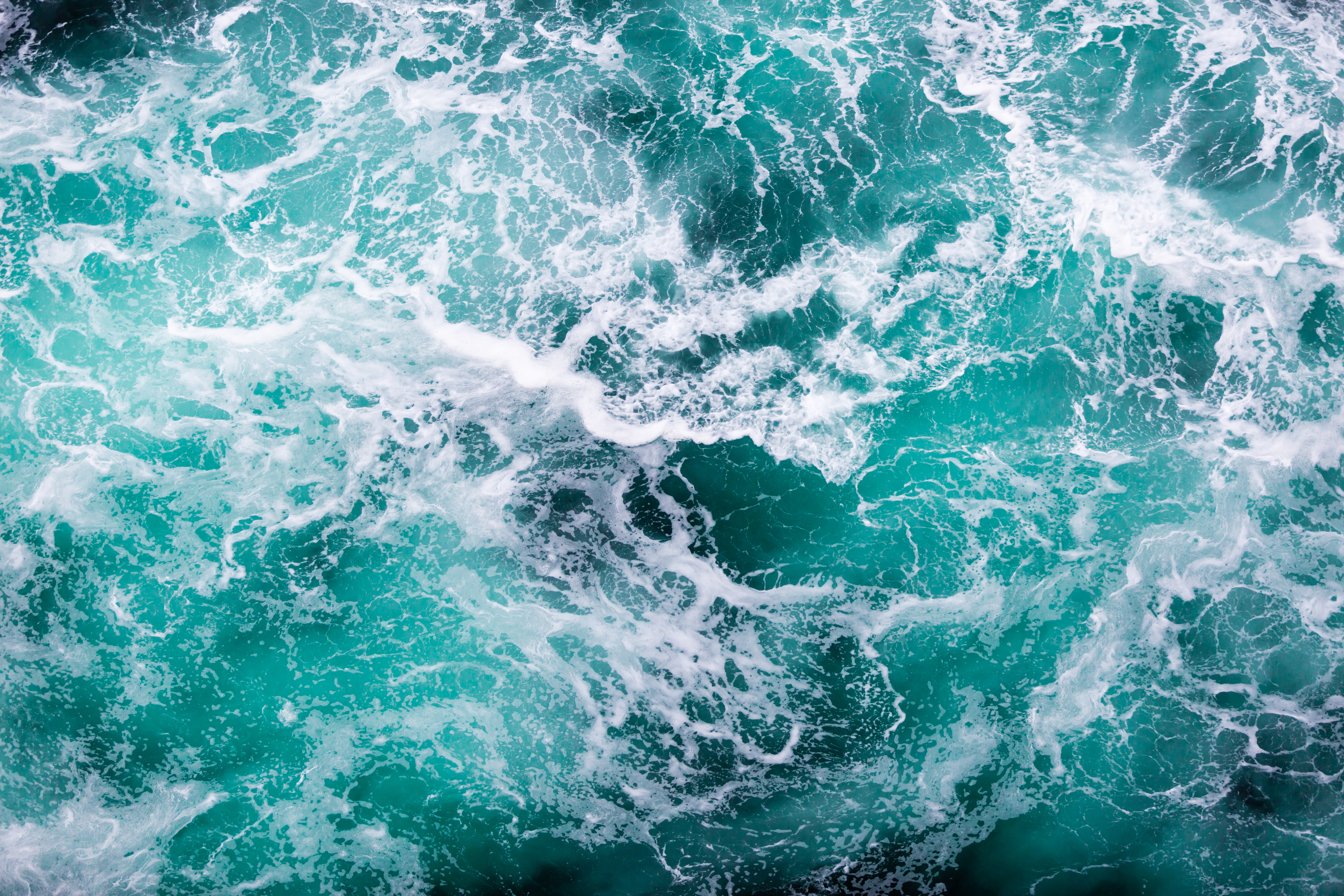 Aqua coloured waves in the water with white sea foam